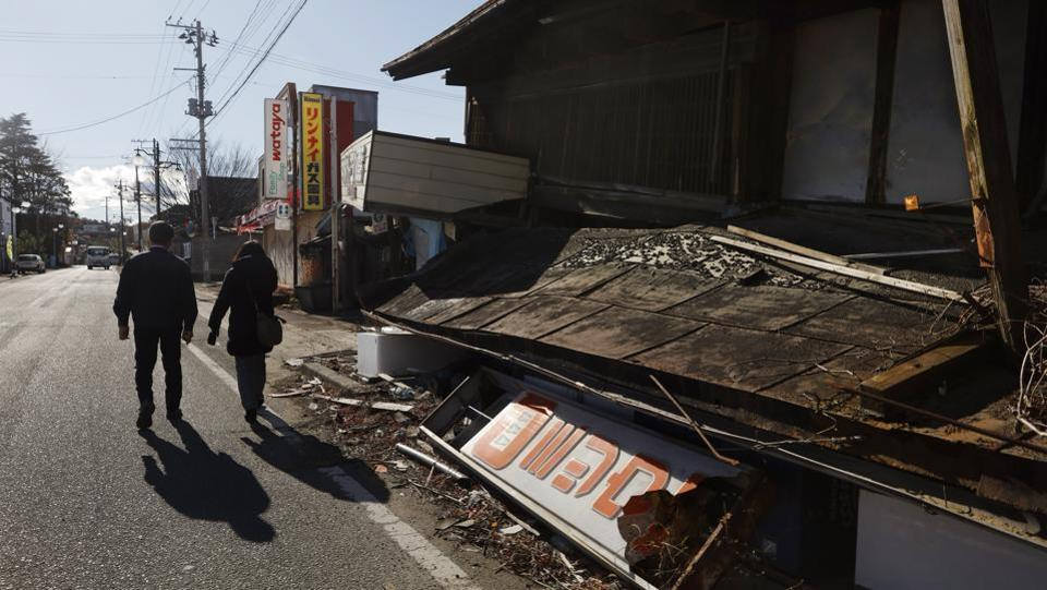 Former town officials and evacuees Osumi Muneshige, left, walks with Yukimi Itakura as they visit the abandoned town of Futaba. The radiation that spewed from the plant at one point displaced more than 160,000 people. Futaba is the only one of 12 radiation-hit towns that remains a virtual no-go zone. Only daytime visits are allowed for decontamination and reconstruction work, or for former residents to check their abandoned homes. (Jae C. Hong / AP)