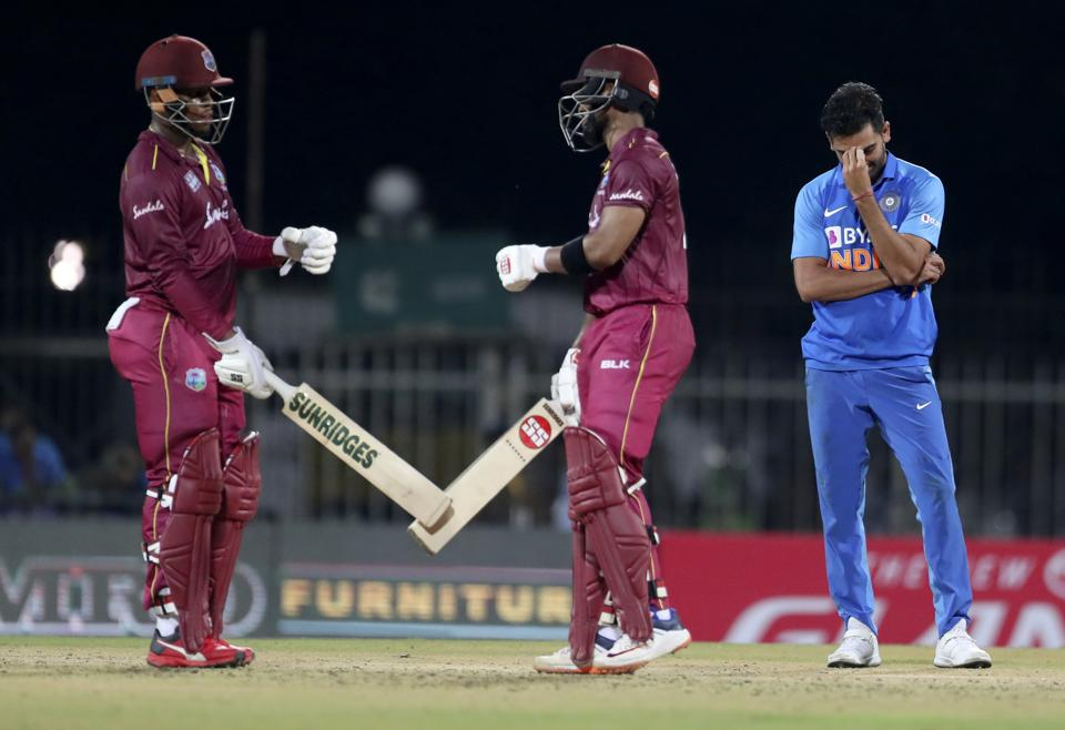 Deepak Chahar, right, reacts as West Indies' Shimron Hetmyer, left, and batting partner Shai Hope celebrate scoring runs. (AP)