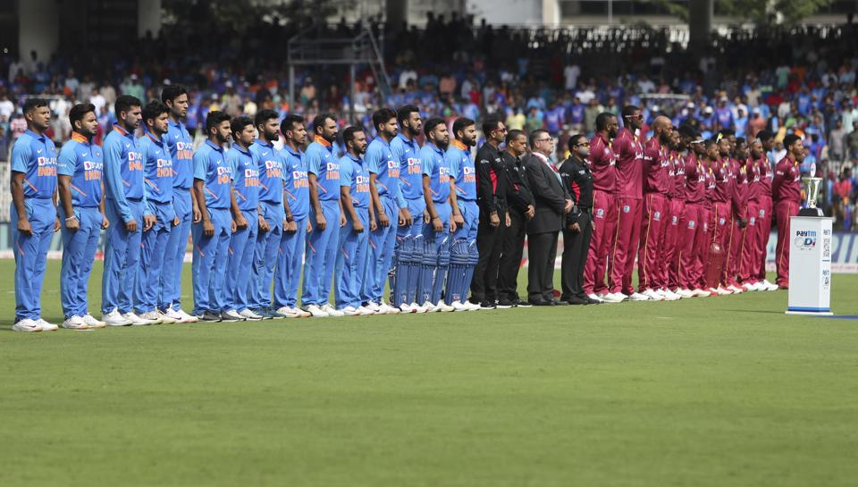 Players of India, left, and West Indies stand for their national anthems before the start of their first one day international cricket match in Chennai, India. (AP)