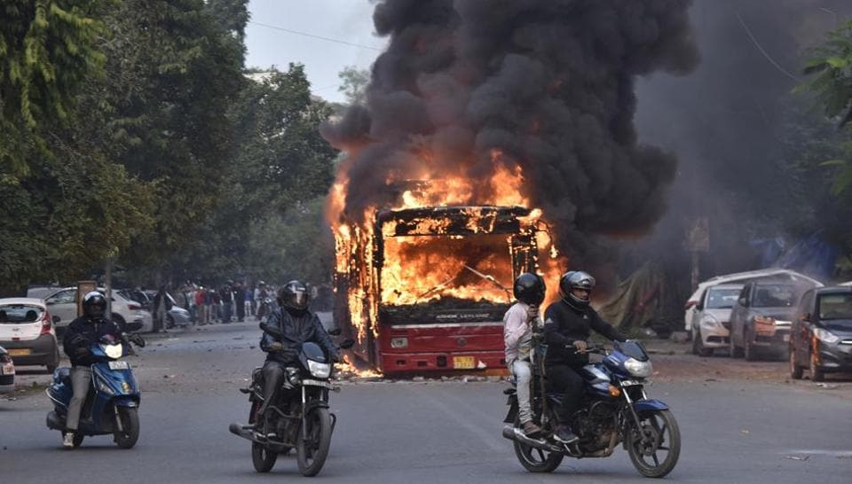 A burning bus is seen after it was set on fire by demonstrators during a protest against a the Citizenship amendment Act (CAA) at New Friends Colony, in New Delhi on Sunday.
