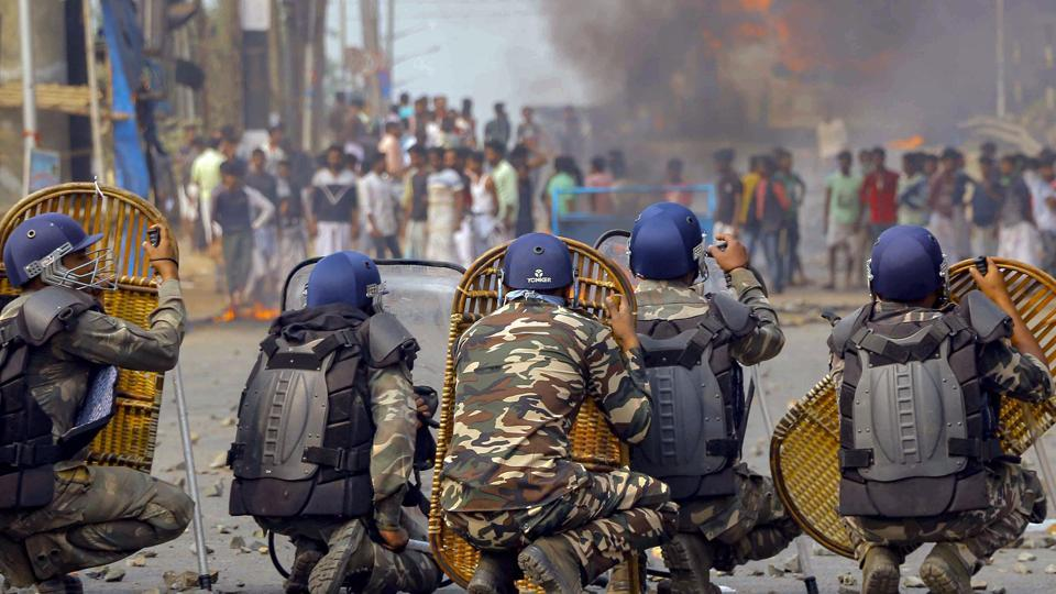 Police jawans try to protect themselves as protestors throw stones on them during an agitation against the Citizenship Amendment Bill (CAB) at Santragachi in Howrah district of West Bengal on Dec 14, 2019.
