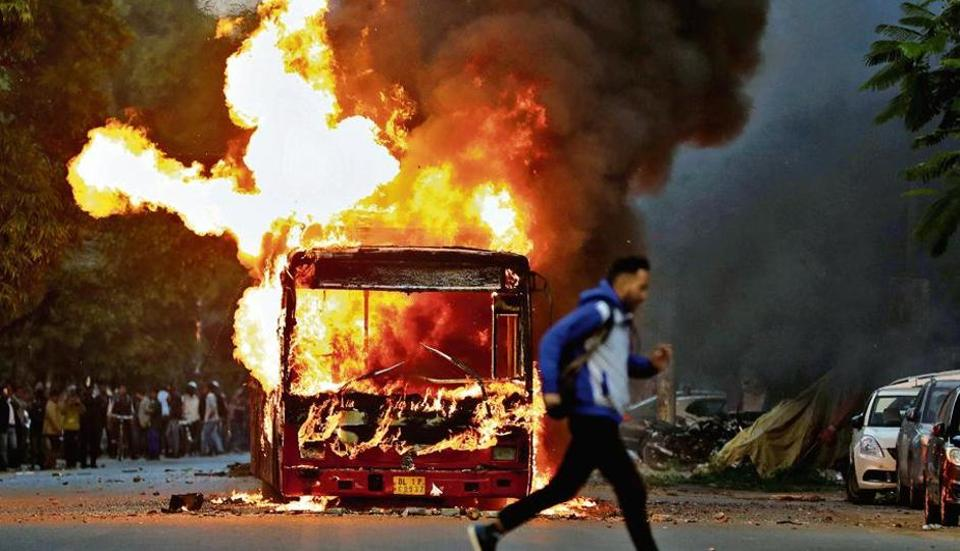 A man runs past a bus that was set on fire by protesters near New Friends Colony in New Delhi on Sunday.