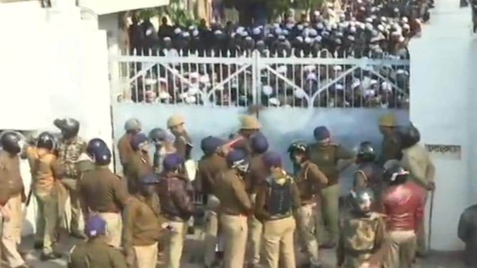 Police close gate of Nadwa college where students protested against the new citizenship law.