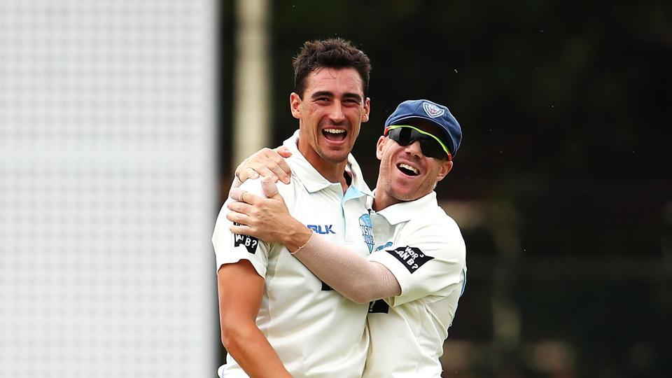 Mitchell Starc celebrates with David Warner during a Sheffield Shield match.