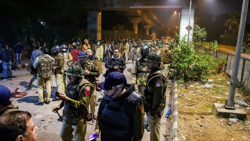 Policemen stand guard near Jamia Millia Islamia following the protests against Citizenship Amendment Act, in New Delhi, Sunday, Dec. 15, 2019.