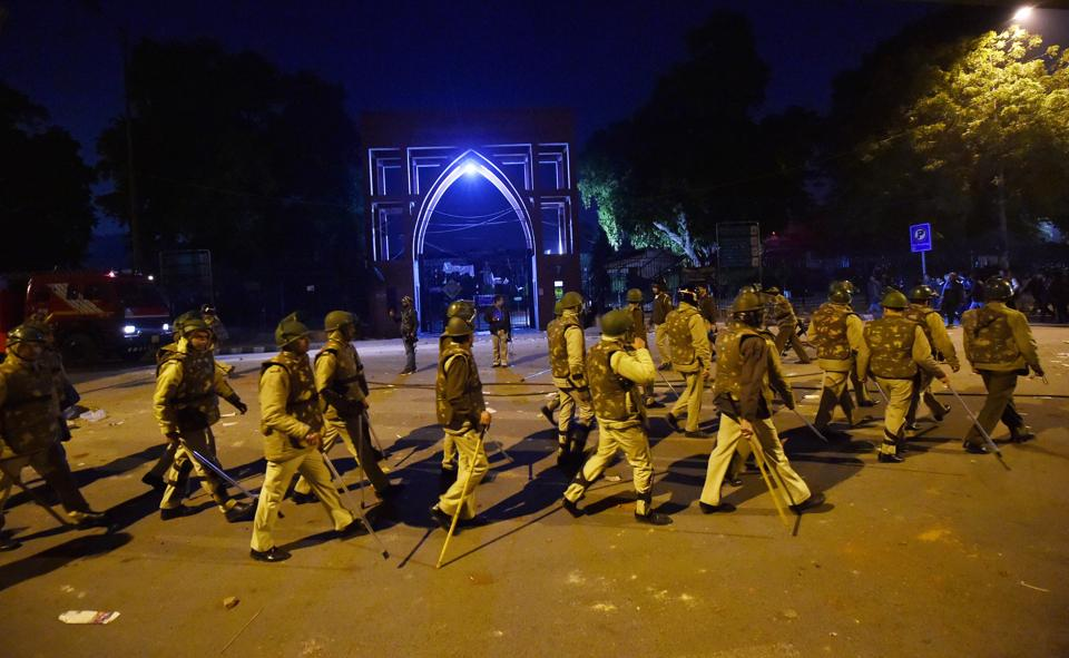 Policemen stand guard near Jamia Millia Islamia following the protests against the new citizenship law in New Delhi on Sunday.
