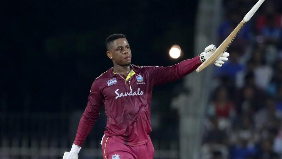 West Indies' Shimron Hetmyer raises his bat to celebrate scoring a century.