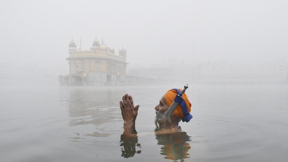 A pilgrim at the sarovar of the Golden Temple in Amritsar on a foggy Wednesday morning. The city recorded a low of 6.4 degrees Celsius.