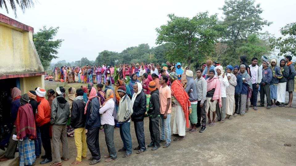 Voters stand in queue to cast their votes at a polling booth during the 4th phase of Jharkhand Assembly Election.