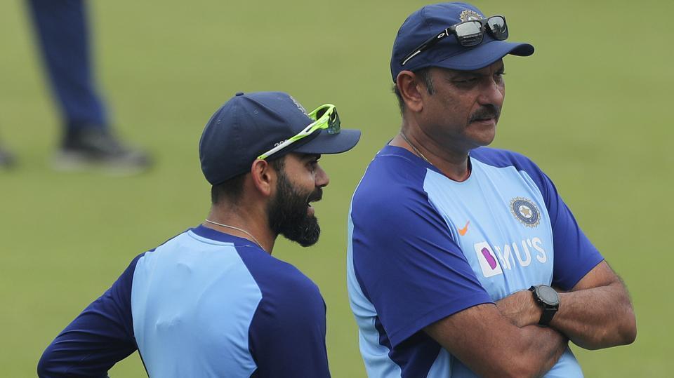 Indian cricket captain Virat Kohli, left, speaks with coach Ravi Shastri during a training session.
