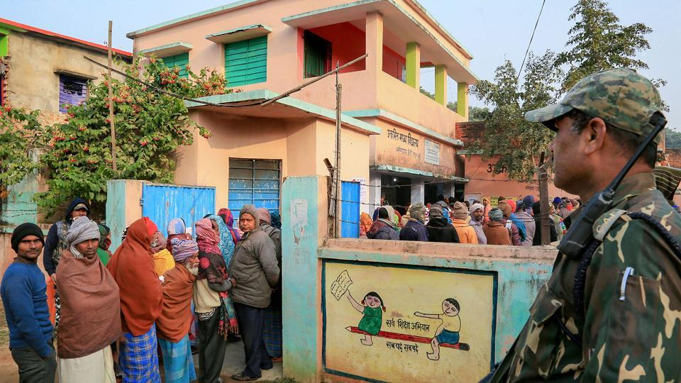 A security person stands guard as voters queue up to cast votes during the fifth phase of the Jharkhand Assembly elections, in Godda district, Friday, Dec. 20, 2019.
