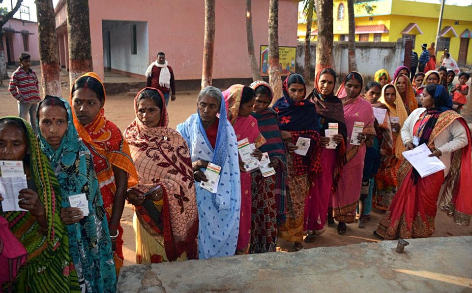 People display their ID cards as they wait in a queue to cast their vote during the fifth phase of Jharkhand Assembly Election, in Dumka on Friday.