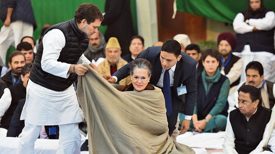 Congress MP Rahul Gandhi drapes a shawl around Congress interim President Sonia Gandhi during the sit in dharna against CAA and NRC, outside Rajghat, in New Delhi