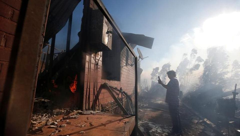 A man uses his cell phone to take a photo of his burning house during a fire in Valparaiso, Chile, December 24, 2019.