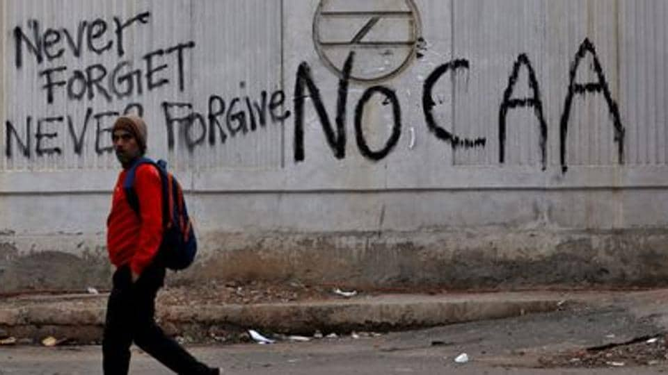 A man walks past a graffiti during a protest against a new citizenship law.