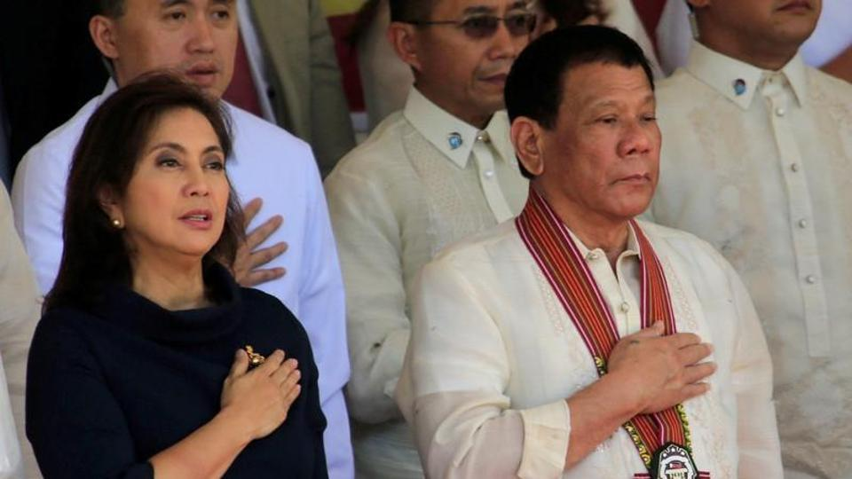 President Rodrigo Duterte and Vice-President Leni Robredo stand at attention for the national anthem during the Philippine National Police Academy graduation ceremony in Camp Castaneda. Duerte's deadly war on drugs -- backed by many Filipinos but condemned by critics who say it is a war crime -- has claimed at least 5,500 lives, however, watchdogs say the actual toll is at least four times higher.