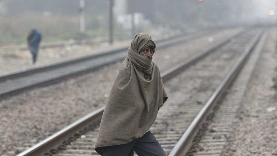 A man wrapped in a shawl crosses a railway track oh Thursday as the national capital witnesses intense cold conditions.