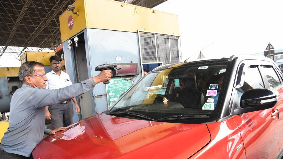 An official scanning FASTag at the toll plaza at Somatnephata near Talegaon in Pune.