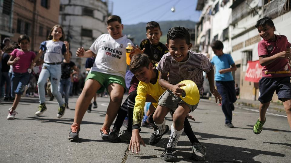 Children play during a sports event organised by members of the Caracas FC soccer club, in Catia, one of the poorest slums in Caracas, Venezuela. When the Caracas Football Club plays, its supporters leave their ideological preferences and socioeconomic differences behind, joining together to support and take care of each other inside and outside the stadium. (Matias Delacroix / AP)