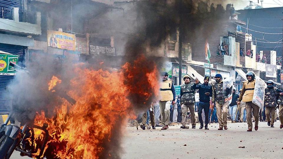 Smoke rises from a burning vehicle during a protest against the CAA in Muzaffarnagar