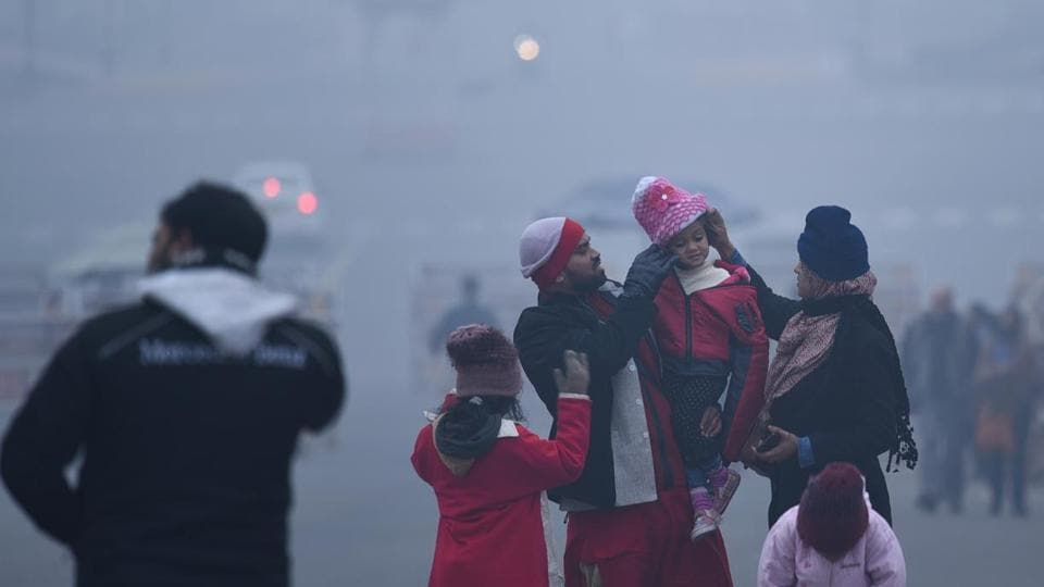 People out on a cold and foggy morning at Rashtrapati Bhawan in New Delhi