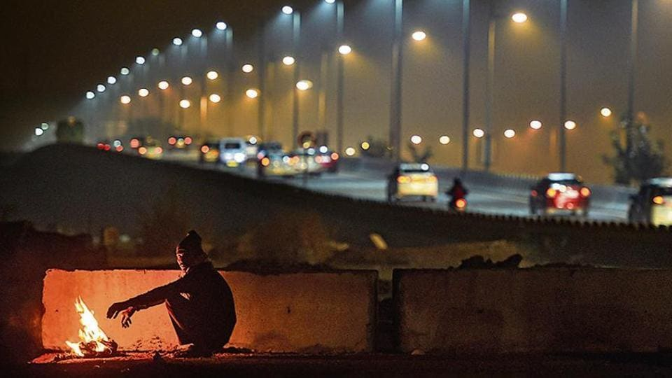 A man warms himself by a bonfire as cars ply in the background on a cold and wintry night, in New Delhi.