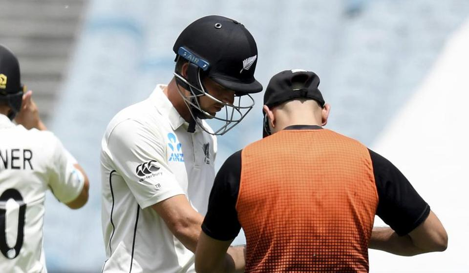 New Zealand's Trent Boult, center, has his hand attended to during their cricket test match against Australia in Melbourne