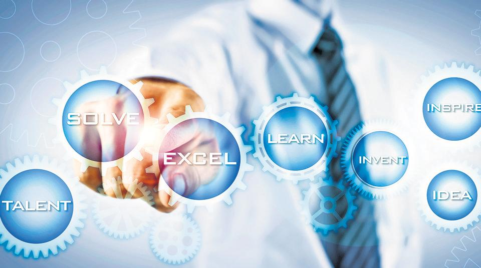 A businessman touches a digital screen on font of him made of cogwheels which contain strategic business key wordings such as Solve, Excel, Talent, Learn, Invent, Idea and Inspire. A slight flares lights up the connection between the Solve and Excel gears.