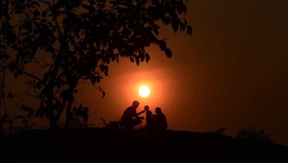 A family spends time under a tree on a cold evening near Parvati road in Pune on Friday.