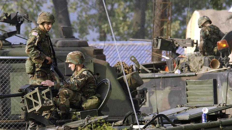 In this Oct. 6, 2004, file photo, US Army soldiers stand guard on the armored vehicles at the their base in Dongducheon, South Korea.