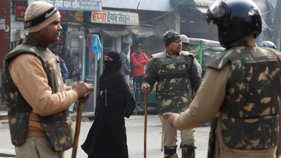 A woman walks past policemen in riot gear on a street in Meerut, Uttar Pradesh. Image used for representational purpose only.