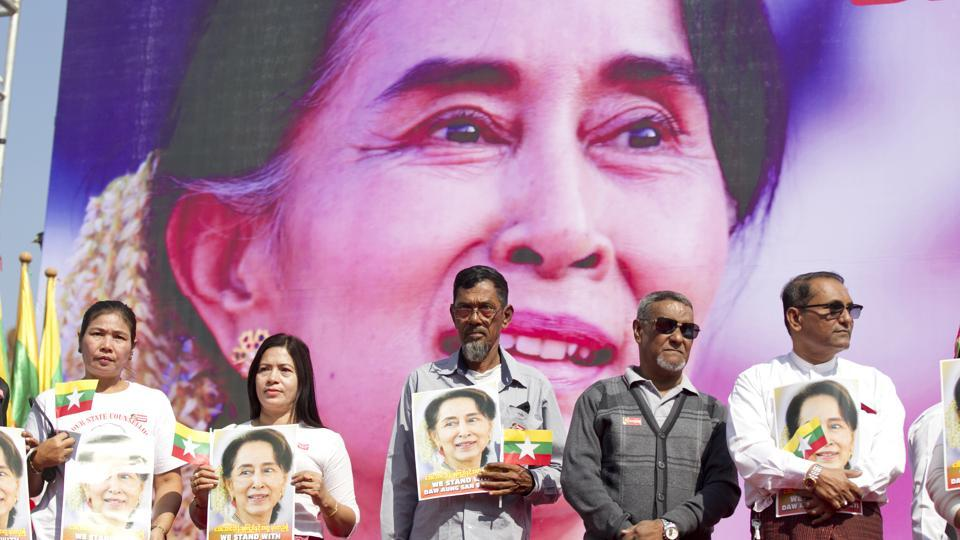 In this Tuesday, Dec. 10, 2019 file photo, Members of Myanmar Muslims community hold portraits of Myanmar leader Aung San Suu Kyi to pray as they gather in front of City Hall in Yangon, Myanmar.