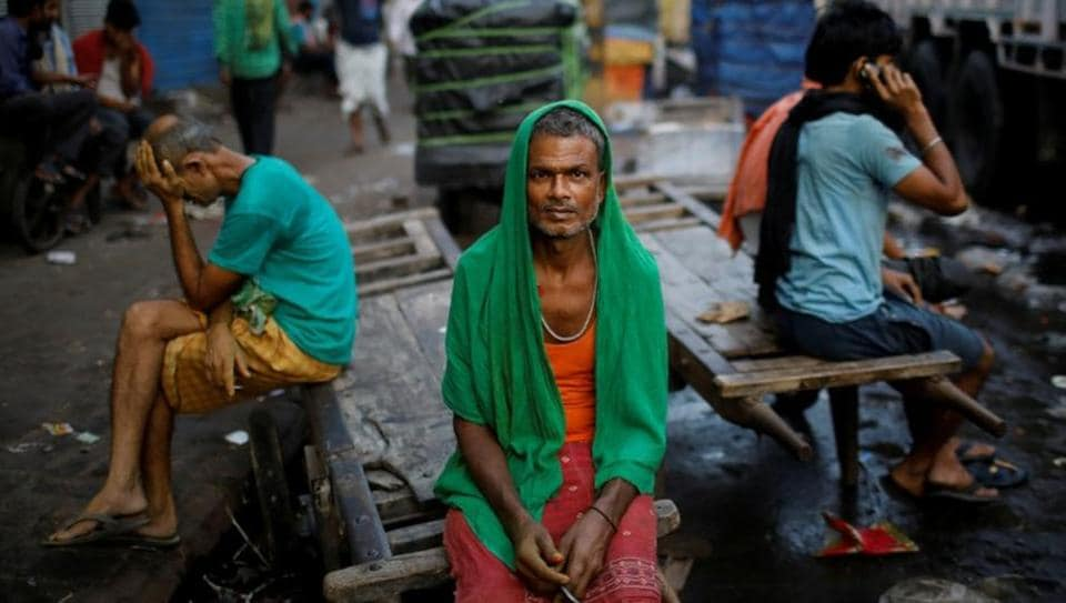 Migrant labourers sit on a handcart as they wait for work at a wholesale market in the old quarters of Delhi.