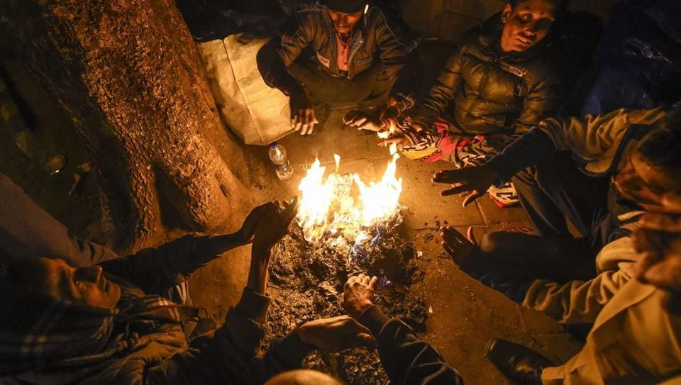 Workers warm themselves at a bonfire on a cold winter in in New Delhi on Saturday, Dec. 28, 2019.