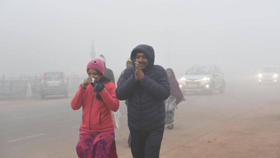 People are seen wearing warm clothes amid dense fog on a cold morning, at Rajpath, New Delhi, on Monday.