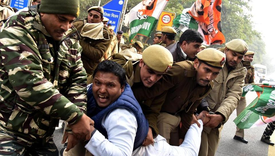 Police personnel detains an Indian youth  supporter during a protest against the CAA on 29 December.