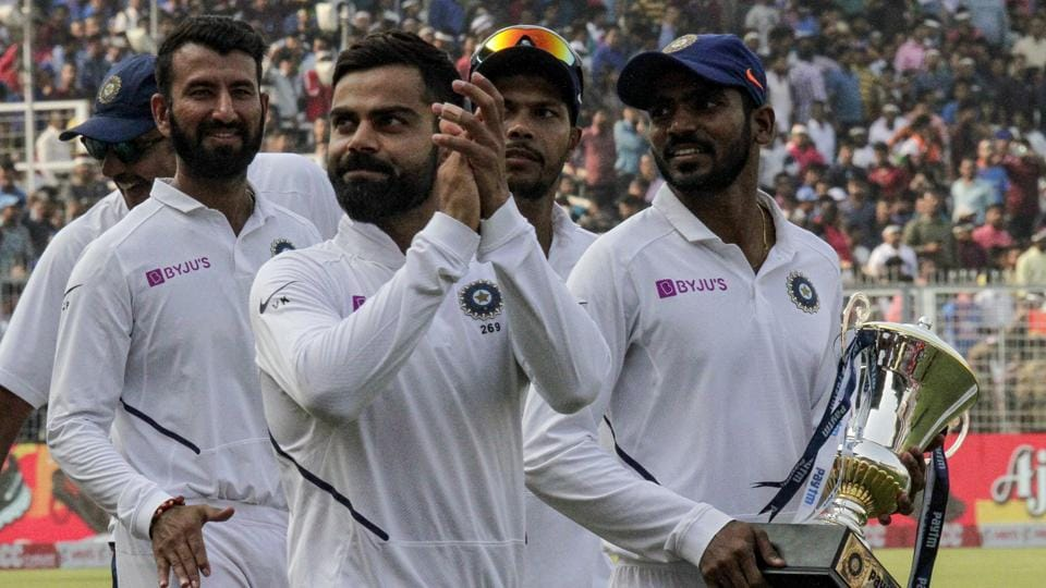 India's captain Virat Kohli applauds as he leads his team in a victory lap.