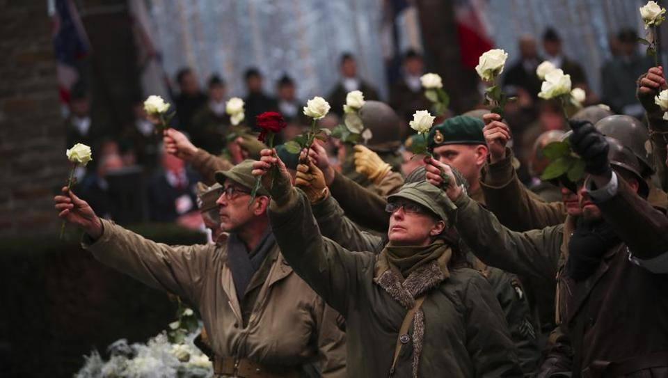 Actors hold up flowers as they perform during a ceremony to commemorate the 75th anniversary of the Battle of the Bulge at the Mardasson Memorial in, Belgium on 16 December.