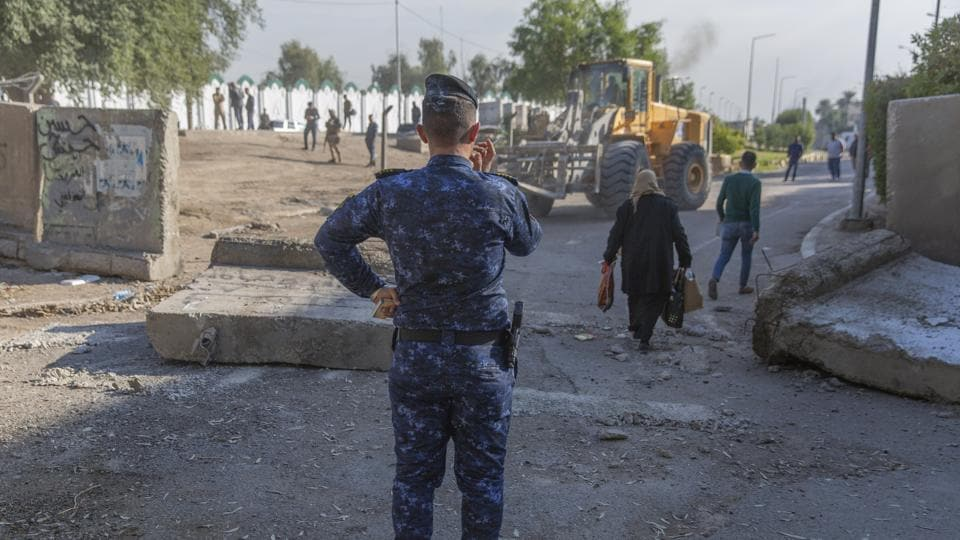 Three rockets fell on Baghdad airport on Friday. An Iraqi police officer instructs a bulldozer while Iraqi security forces remove cement blocks and opened the streets, that were closed for security concerns, around the Green Zone in Baghdad, Iraq, Thursday.