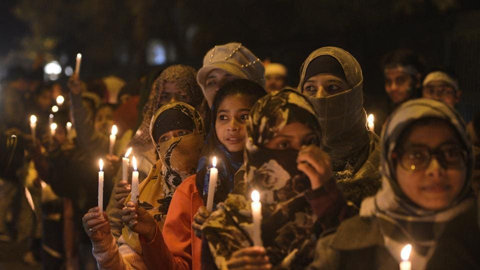 People holding candles march as part of an ongoing protest against the Citizenship Amendment Act (CAA) and National Register of Citizens (NRC), at Jamia Millia Islamia University, in New Delhi.