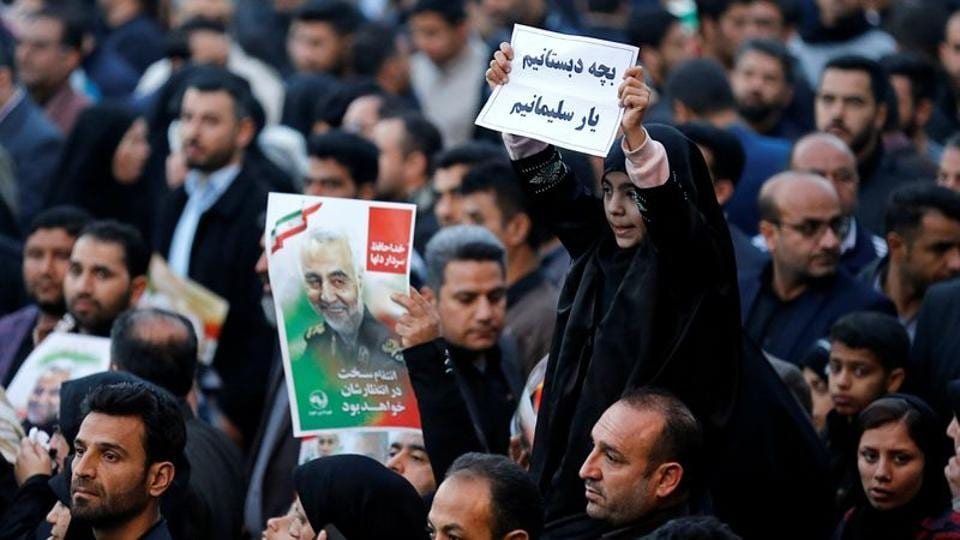 A girl holds a sign during a funeral procession for Iranian Major-General Qassem Soleimani, head of the elite Quds Force, and Iraqi militia commander Abu Mahdi al-Muhandis, who were killed in an air strike at Baghdad airport, in Ahvaz, Iran.
