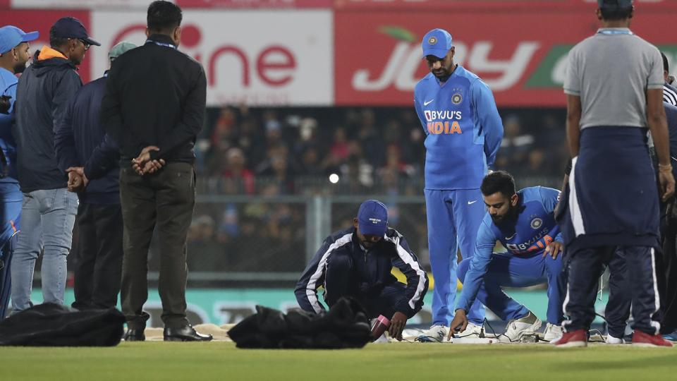 Indian captain Virat Kohli, second from right, inspects the pitch after the rain