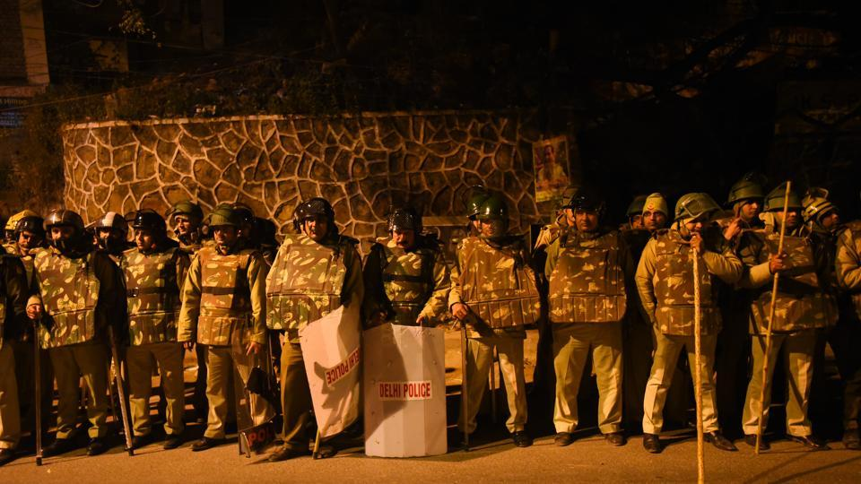Police personnel are seen outside the main gate of JNU campus,  Monday, December 6, 2020.