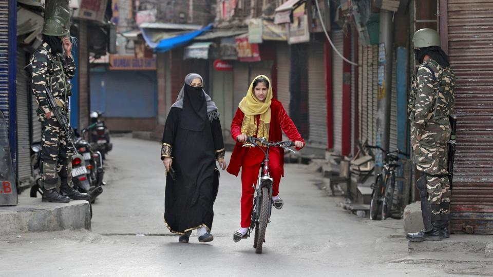 A Kashmir girl rides her bike past security force personnel standing guard in front closed shops in a street in Srinagar.