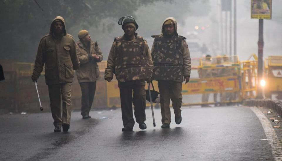 Police personnel are seen outside the main gate of JNU campus in New Delhi, India, on Wednesday, January 8, 2020.