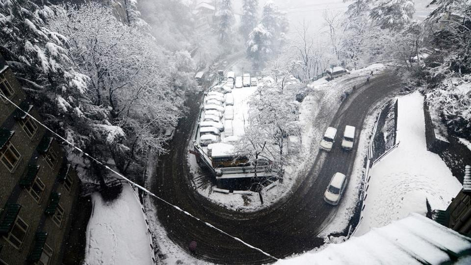 Traffic moves cautiously on a slippery road after heavy snowfall. Shimla Police on Thursday evening put out a Facebook post alerting tourists not to travel towards Kufri and Mashobra as the roads were still snow-bound. Shimla Met Centre recorded the lowest temperature on Thursday in Lahaul-Spiti district's administrative centre Keylong at minus 17.6 degrees Celsius. (Deepak Sansta/HT Photo)