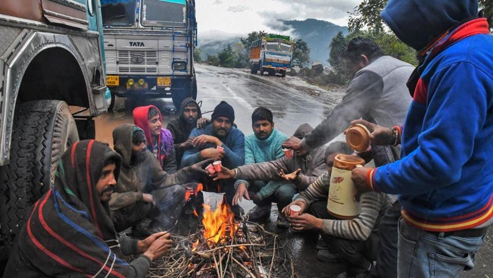 Drivers warm themselves around a bonfire by the roadside, near Swarghat. At least 174 are blocked in Lahaul and Spiti district, 100 in Kullu, 97 in Mandi, 66 in Kinnaur, 52 in Chamba and 43 in Sirmaur. (PTI)