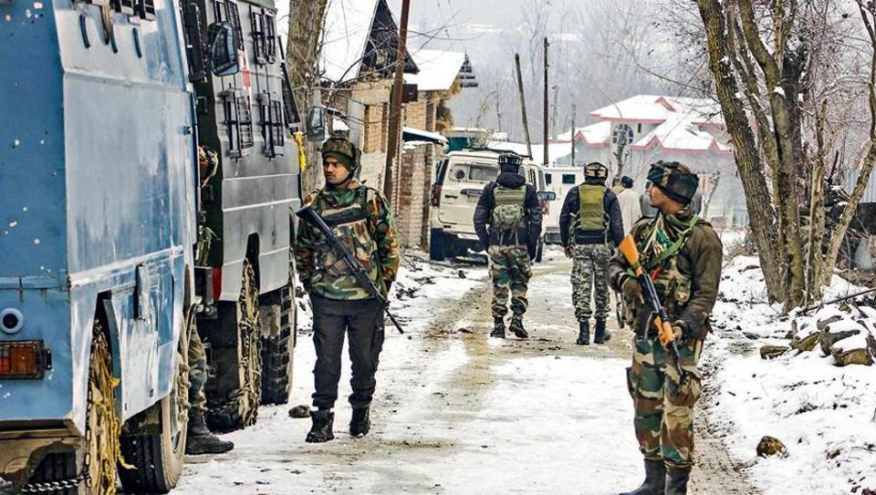 Army personnel take positions near a house where the terrorists were hiding at Gulshanpora in Tral area of south Kashmir on Sunday.