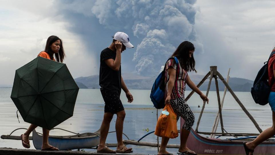Residents walk past wooden boats as Taal volcano erupts in Tanauan town, Batangas province, south of Manila, Philippines. Clouds of ash blew far north of the Philippines' Taal volcano, reaching Manila, the country's bustling capital, and forcing the shutdown of its main airport after lava gushed out of the mountain on Monday. Thousands of villagers were fleeing to safety, but officials say the number could swell to hundreds of thousands. (Ted Aljibe/AFP)