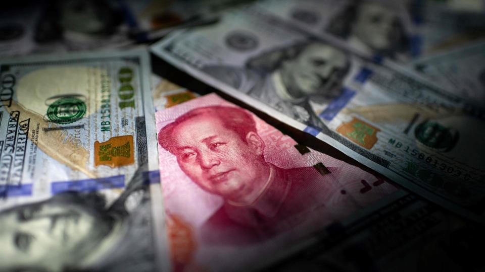 A photo illustration of a Chinese 100 yuan note (C) and US 100 notes. China's trade surplus with the United States narrowed last year as the world's two biggest economies exchanged punitive tariffs in a bruising trade war, data showed on Tuesday, just as the two prepared to sign a deal dialling down tensions. (Nicolas Asfouri / AFP)